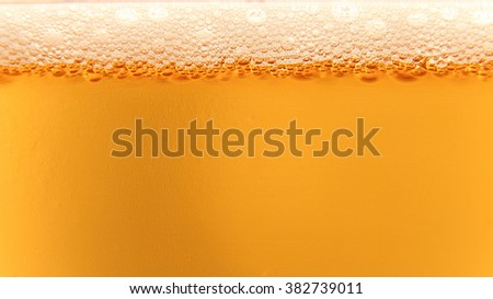 Macro shot of beer and beer foam in glass. Ideal for use as a background or backdrop in your project. - stock photo