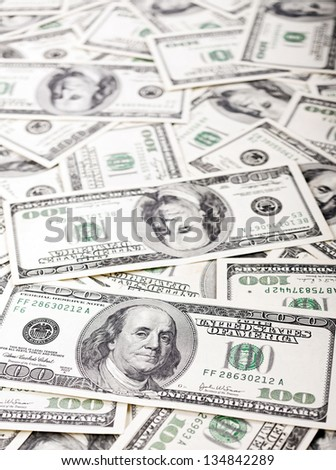 Macro shot of Benjamin Franklin's portrait on a 100 US$ money note, with defocused background of many more identical money notes in a mess. - stock photo