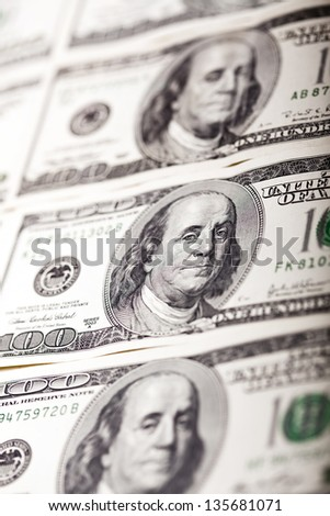 Macro shot of Benjamin Franklin's portrait on a 100 US$ money note, with two more notes above and below it. Shallow depth of field.
