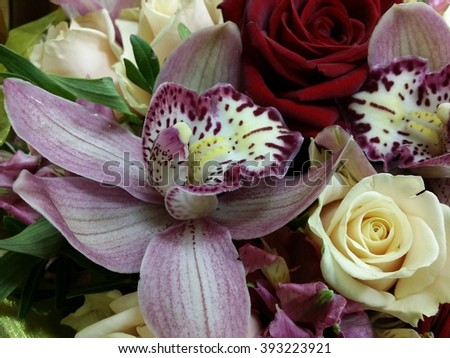 Macro shot of boquet  with rose and red orchid flowers on the desk - stock photo