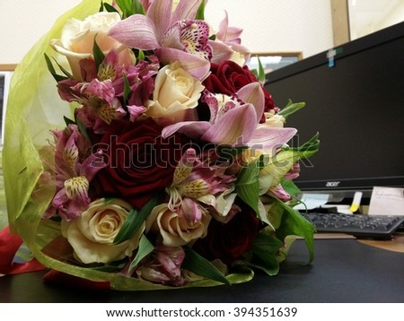 Macro shot of bouquete with rose and red orchid flowers on the desk - stock photo