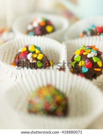 Macro shot of chocolate candies with colorful sprinkles on top - stock photo