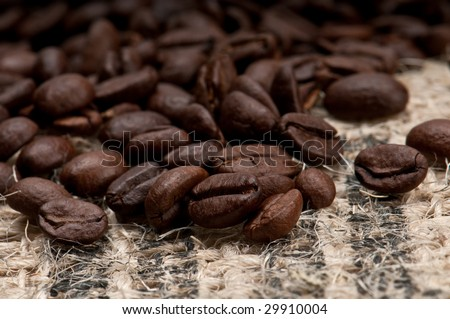Macro shot of coffee beans over burlap. - stock photo