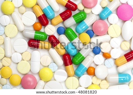 Macro shot of colored pills and capsules heap isolated  on white background