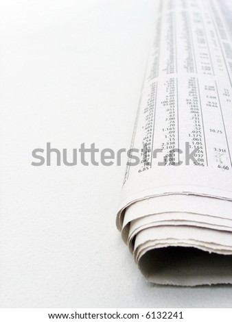Macro shot of daily financial data in a newspaper on a pale desk. This is not an isolation shot; there is texture evident in the background. - stock photo