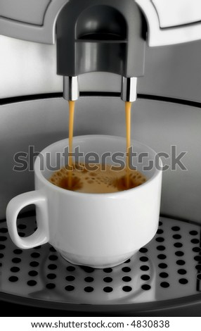 Macro shot of espresso flowing into a cup. - stock photo