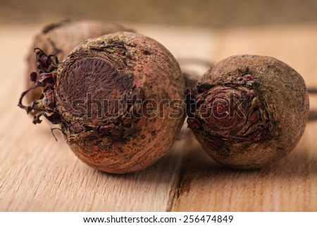 Macro shot of freshly harvested beets from an organic farm on cedar wooden planks - stock photo
