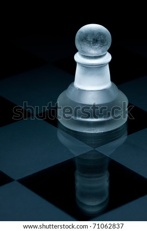 Macro shot of glass chess pawn against a black background - stock photo