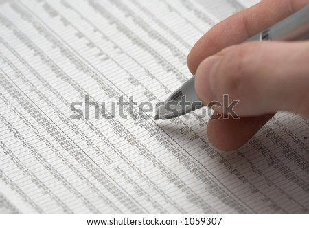 Macro shot of hand holding a shiny pen over a spreadsheet - stock photo