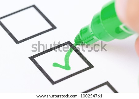 Macro shot of human hand drawing green check mark in checklist box - stock photo