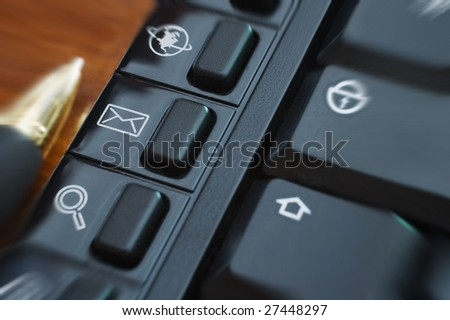 Macro shot of multimedia keyboard button with shallow depth of field and pen. Zoom effect. - stock photo