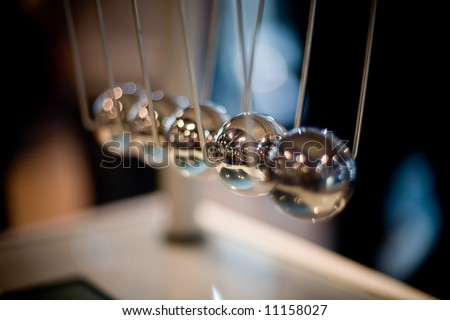 Macro shot of newton's cradle with shallow depth of field (only second ball is in focus) - stock photo