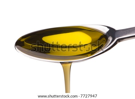 Macro shot of Olive oil poured from a spoon - stock photo