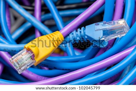 Macro shot of plugs on cat5e cables of many colors on top of tangle of wires - stock photo
