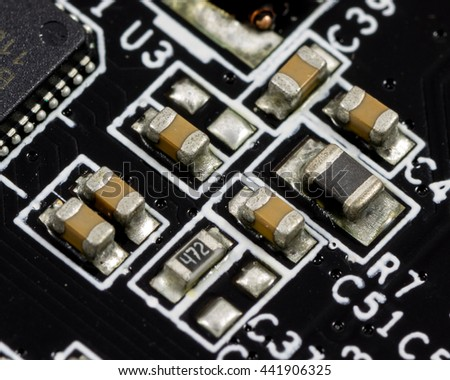 Macro shot of printed circuit board (PCB) with capacitors, IC, and resistors. - stock photo