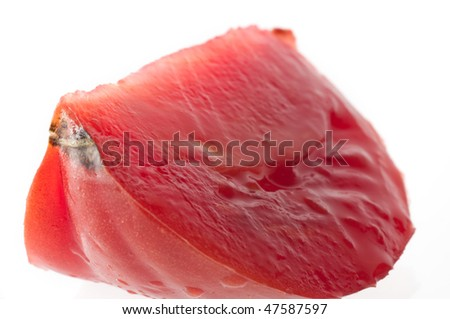 Macro shot of red tomato wedge isolated against white background
