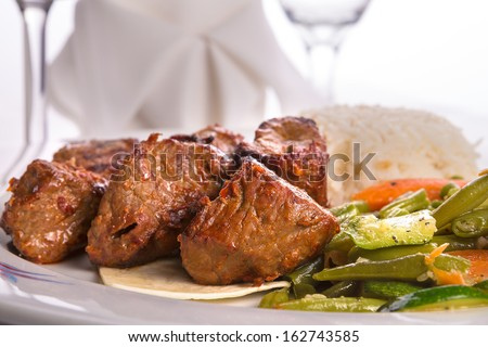 Macro shot of shish kebabs garnished with vegetables and rice pilaf, napkin and vine glass on the background - stock photo