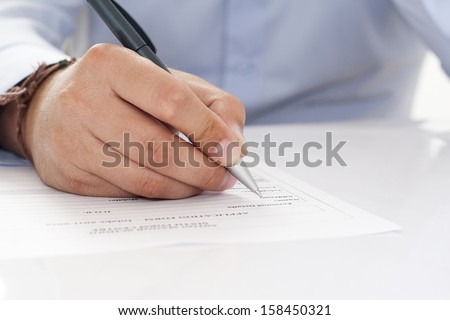 Macro shot of someone signing a contract. Focus is on the signature and the end of the pen. - stock photo