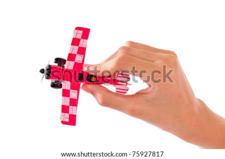 Macro shot of the hand of a kid holding a toy plane isolated on white - stock photo