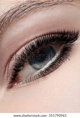 Macro shot of woman's beautiful green eye with extremely long eyelashes. Sexy view, sensual look