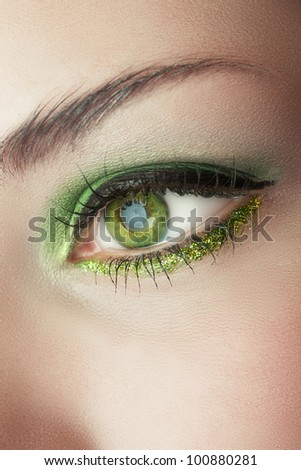 macro shot of woman's eye with green smoky eyeshadow and gold glitter . - stock photo