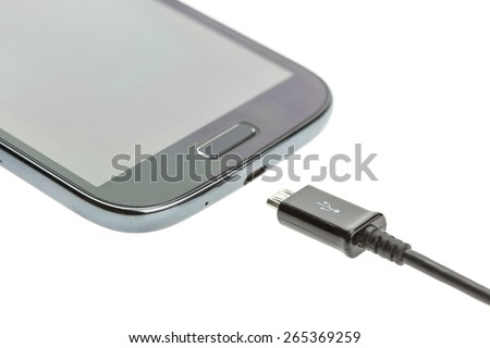 Macro Smartphone with charger cable isolated on white background - stock photo