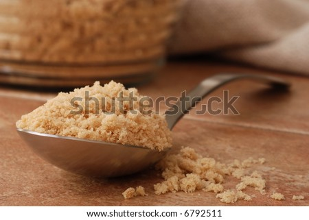 Macro still-life of serving spoon overflowing with brown sugar onto color coordinated porcelain tile. Glass canister of brown sugar and homespun cloth out of focus in the background.  Shallow dof - stock photo
