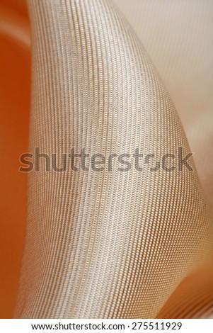 macro texture of satin fabric peach color studio  - stock photo