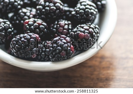 Macro view of a bowl of blackberries on wooden table (Shallow DOF) - stock photo