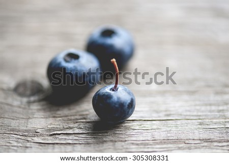 Macro view of a group of blueberries on rustic wooden table, focus on single blueberry stem, shallow DOF - stock photo