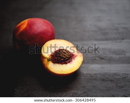 Macro view of a group of juicy, ripe nectarines on rustic, wooden table, shallow DOF - stock photo