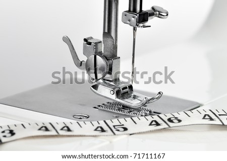 Macro view of a sewing machine mechanism and a measuring tape - stock photo
