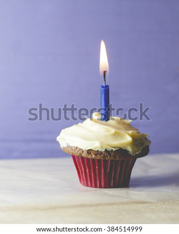 Macro view of a single cupcake with blue candle and purple background