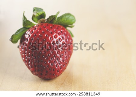 Macro view of a single strawberry on a wooden table (Shallow DOF) - stock photo