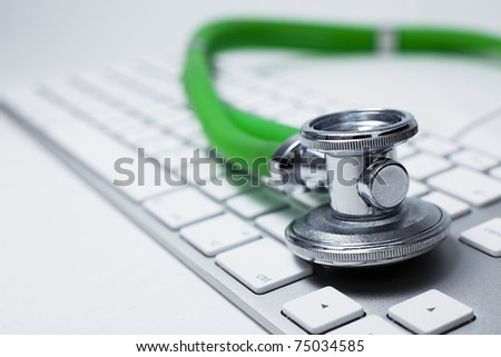 Macro view of a stethoscope on computer keyboard. - stock photo
