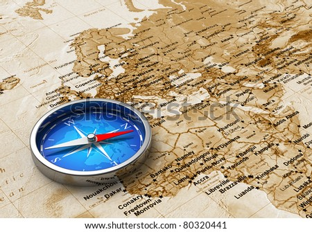 Macro view of blue metal compass on the old world map
