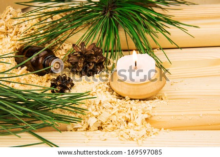 Macro view of candle, cones, glass bottle of oil, wooden sawdust, green pine twigs and logs - stock photo