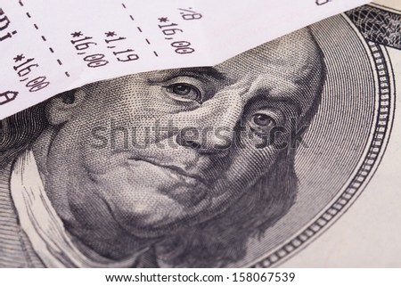 Macro view of cash register receipt and one hundred dollar bill. - stock photo