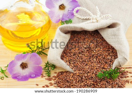 Macro view of flax seeds in flax sack and glass bottle of flax oil with flowers isolated on white background - stock photo