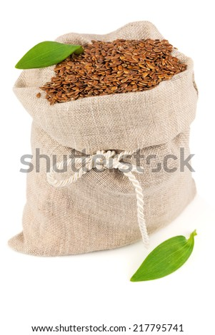 Macro view of flax seeds in flax sack with leaves isolated on white background - stock photo
