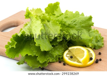 Macro view of fresh lettuce slices of lemon and black pepper on the cutting board on white background - stock photo