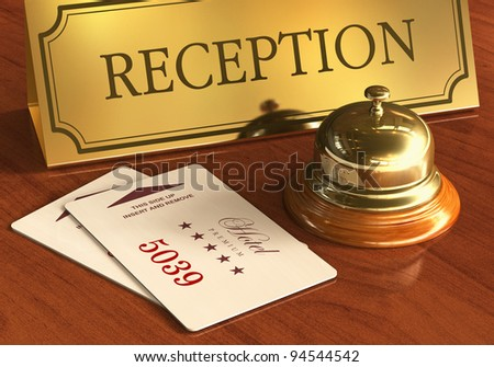 Macro view of golden service bell and room access cardkeys on wooden reception desk in hotel - stock photo