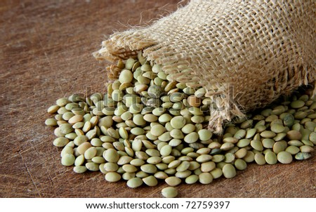 Macro view of lentils on wooden background - stock photo