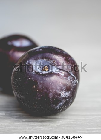 Macro view of purple plums on a rustic wooden table, shallow DOF  - stock photo