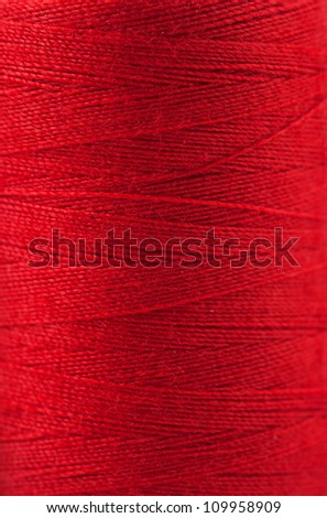 Macro view of red thread wound on a spool - stock photo