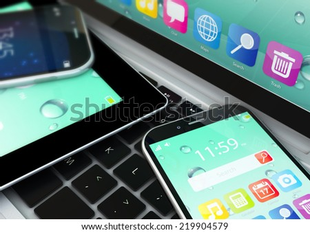 macro view of tablet computer and touchscreen smartphones with colorful interfaces on laptop notebook PC - stock photo