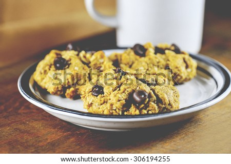 Macro view of three chocolate chip cookies on a plate with a mug of milk, shallow DOF - stock photo