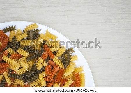Macro view of tri-color rotini rainbow pasta on rustic wooden table surface, shallow DOF - stock photo