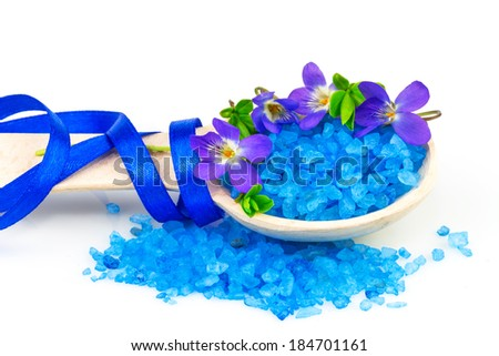Macro view of wooden spoon with blue bath salt and spring flowers isolated on white background - stock photo