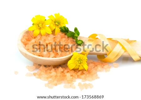 Macro view of wooden spoon with orange bath salt and autumn flowers isolated on white background - stock photo